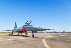 Military fighter jet aircrafts parked on runway in airforce. On blue sky background royalty free stock photos