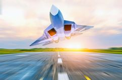 Military fighter jet flies at high speed over the taxiway at the airport. Royalty Free Stock Photos