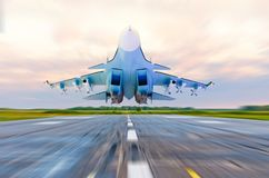 Military fighter jet flies at high speed over the taxiway at the airport. Military fighter jet flies at high speed over the taxiway at the airport Stock Photo