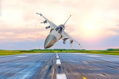 Military fighter jet flies at high speed over the taxiway at the airport. Royalty Free Stock Photo