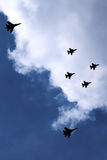 Military Fighter Jets Flying in a Formation. Silhouette of military fighter jets flying in a formation in the sky Royalty Free Stock Photography