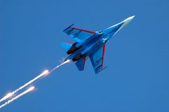 Military fighter su-27 2. Military fighter su-27 fireworks on blue sky Royalty Free Stock Image