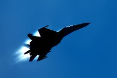 Military fighter su-27 silhouette. Military fighter  su-27 silhouette on blue sky Royalty Free Stock Image