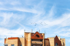 Military fighters and attack planes over house Royalty Free Stock Images
