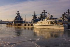 Military fleet in the city port. Many modern ships of gray color stand in the roadstead near the seaside city. Military fleet, flotilla. Cold season, the water Royalty Free Stock Photo