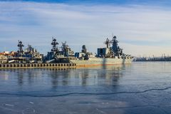 Military flotilla in the roadstead. The blue sea is covered with clear ice. There are several large warships in the harbor. Northern port, the cold season Stock Photography