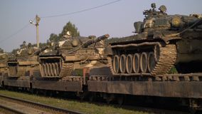 Military gear russian tanks is loaded on to railcars and prepared for cross country transport. CIRCA 2010s - U.S. military gear is loaded on to railcars and stock footage
