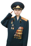 Military girl. 8-year-old girl saluting in her grandfather's full uniform of Russian Army against white background, isolated stock photo