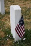 Military gravestone at the Battle of Little Bihorn cemetery. American flag planted next to fallen soldier head stone at the Battle of Little Bighorn cemetery stock images