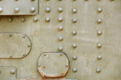 Tank Metal Armor. Military green camouflage metal steam punk background. Real tank armor with rivets, plates and details royalty free stock images