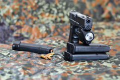 Military handgun with laser/light-module. 9mm military sidearm with a tactical laser/light-module on camouflage Royalty Free Stock Photo