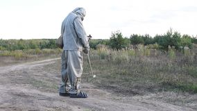 The military in a hazmat suit checks radiation level at the road dosimeter, radiation hazard. Military in a protective suit checks the level of radiation on the stock footage