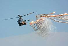 Military helicopter. In fly attack with flares Royalty Free Stock Photos
