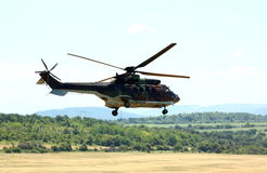 Military helicopter. Flying military helicopter with forest background stock photo