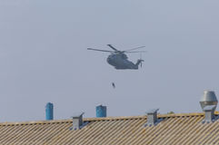 Military helicopter in action. Military helicopter rescue,military deployment ,solder rescue a man from a fabric flue Stock Images