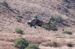 Military helicopter. A camouflaged military helicopter in flight in valley Stock Photo