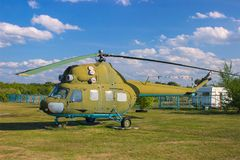 Military helicopter at field. Military helicopter on the land at green field Royalty Free Stock Image