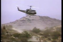 Military helicopter flying over men on horseback in desert stock footage