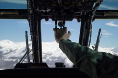 Military helicopter flying through white snowed mountains. Pilot and copilot wearing green flightsuit and helmet view Stock Photo