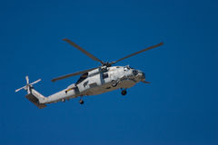 Military helicopter hovering. A military helicopter hovering in clear blue sky Royalty Free Stock Photography