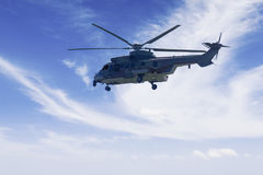 Military helicopter is hovering in the blue sky. Image of military helicopter is hovering in the blue sky while doing patrols Stock Photo