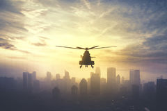 Military helicopter hovering at sunset time. Silhouette of military helicopter hovering over downtown, shot at sunset time Stock Photography