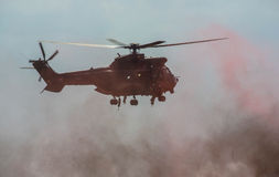 Military Helicopter Hovers in Smoke Stock Photography