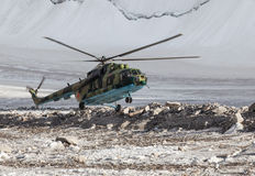 Military helicopter landing on ice of mountain glacier Stock Images