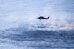 Military helicopter hovering above the river stock photo