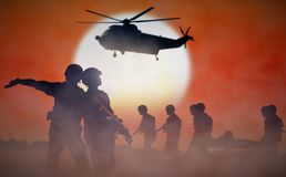 Military helicopter rescue mission during sunset. With soldier waiting on the ground stock photos