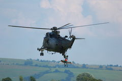 Military Helicopter rescuing injured soldier. A photo close up of a Military helicopter used by the British Royal Navy on a mild english afternoon. Made possible Royalty Free Stock Image