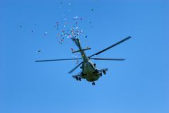 Military helicopter throws festive flyers Stock Photo