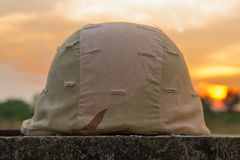 A military helmet. Of desert camouflage with gray sunset background Royalty Free Stock Photos