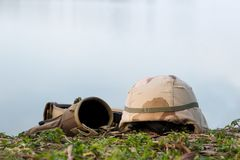 A military helmet of desert camouflage and tactical belt. With blurred river in  background Royalty Free Stock Image