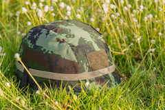 A military helmet of digital green camouflage on green grass background Stock Images