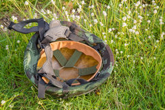 A military helmet of digital green camouflage on green grass background Stock Photo