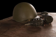 Military helmet, hand grenades and bullets on table Stock Images