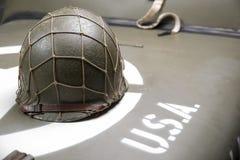 Military helmet on the hood of military vehicle Stock Photos