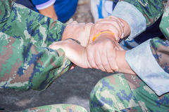 Military holding each others wrists in a circle. Two military holding each others wrists in a circle Stock Photo