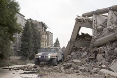 Military hummer in the middle of city ruins, collapsed houses. Military vehicle in the middle of city ruins, collapsed bouildings Stock Photo