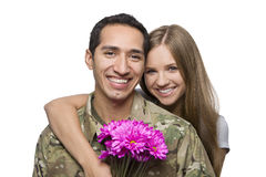 Military Husband and Wife Smile with Flowers. Happy Hispanic serviceman and his spouse royalty free stock photography