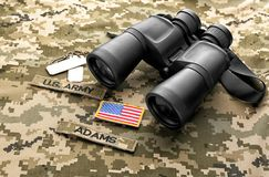 Military ID tags, patches and binocular. On camouflage background Royalty Free Stock Images