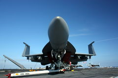 Military Jet Superhornet Navy. Military jet on an aircraft carrier taken from the front of the jet with the wings folded American flag  and dark blue sky in the Stock Image