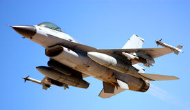 Military jet. Military fighter jet plane F16 armed with guiding missile and rockets ready for fight isolated on a blue sky background