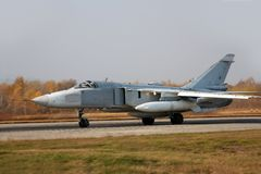 Military jet bomber airplane Su-24 Fencer. On take off and landing royalty free stock photography