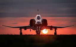 Military jet fighter on runway at sunset
