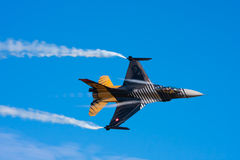 Military jet in flight. F-16 military jet fighter in flight at high speed creating vapor trails stock photo
