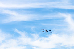 Military low-flying aircrafts in white clouds. Flight of military low-flying aircrafts in white clouds in blue sky Royalty Free Stock Images