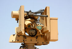 Military machine-gun. A military machine-gun on a robotic mount isolated on a clear blue sky background. CROW system (Common Remotely Operated Weapon Station Stock Photo