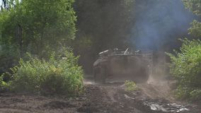 Military machine infantry driving on road at shooting range back view. Army tank on military opertion moving on dirty road slow motion stock video footage
